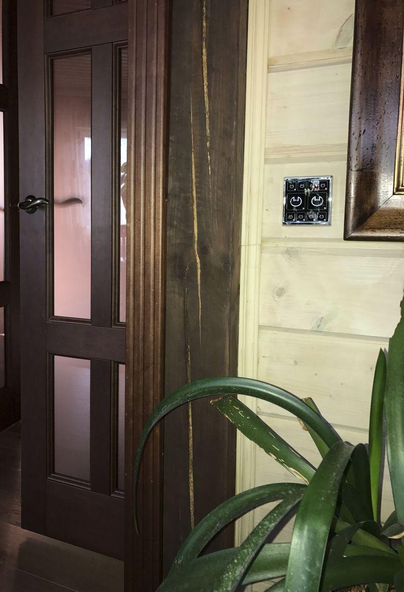 двухклавишный выключатель света в интерьере деревянного дома