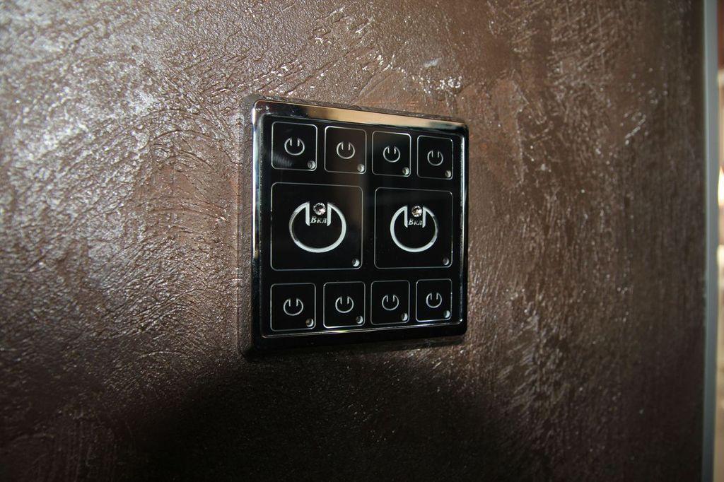Умный современный сенсорный двухклавишный выключатель света в интерьере, выполненном в современном стиле с декоративной штукатуркой